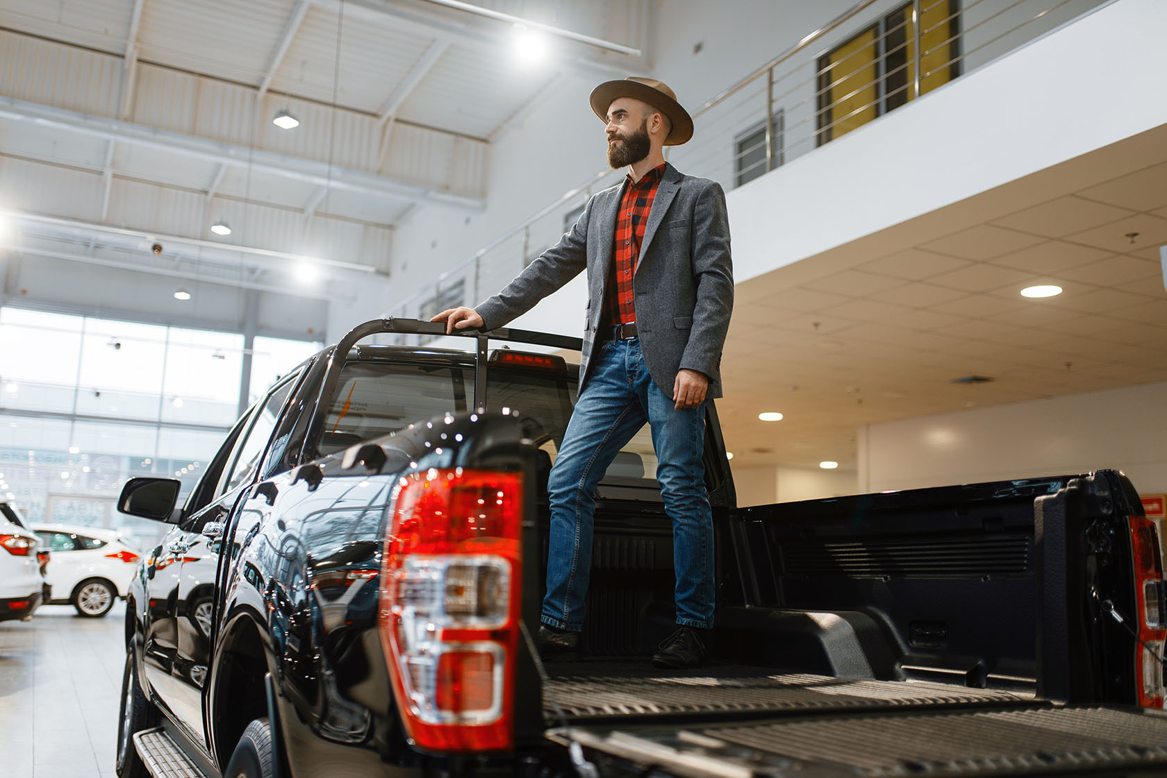Man standing in the back of new pickup truck